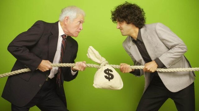 Men pulling tug of war with bag of money on it